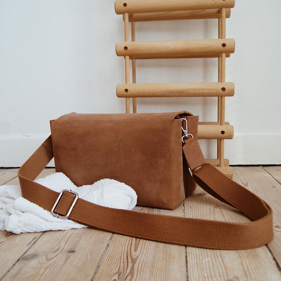 Pusletaske i brun står på gulvet